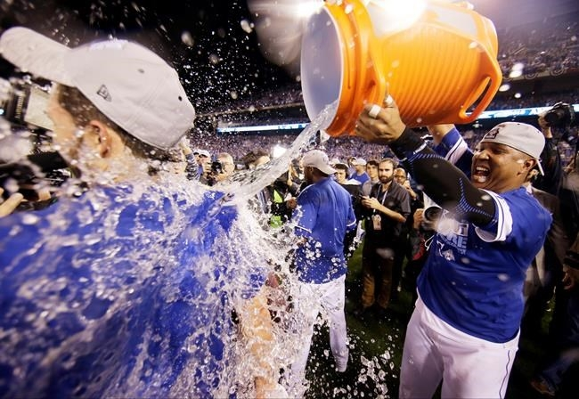 Kansas City Royals catcher Salvador Perez, right, soaks first baseman Eric Hosmer after their 4-3 win against the Toronto Blue Jays in Game 6 of baseball's American League Championship Series on Friday, Oct. 23, 2015, in Kansas City, Mo.