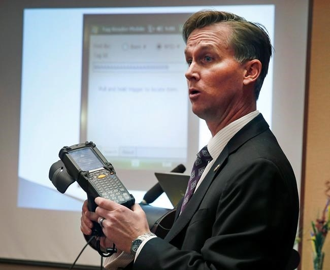 FILE - Lewis Koski, chief investigator of the Colorado Marijuana Enforcement Division, demonstrates a handheld radio-frequency reader, which is part of its new marijuana inventory tracking system, known as MITS, during a news conference, in Denver, Wednesday, Dec. 11, 2013.