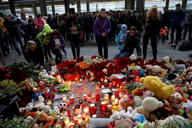 People come to lay flowers and toys at an entrance of Pulkovo airport outside St.Petersburg, Russia, during a day of national mourning for the plane crash victims, on Sunday, Nov. 1, 2015.