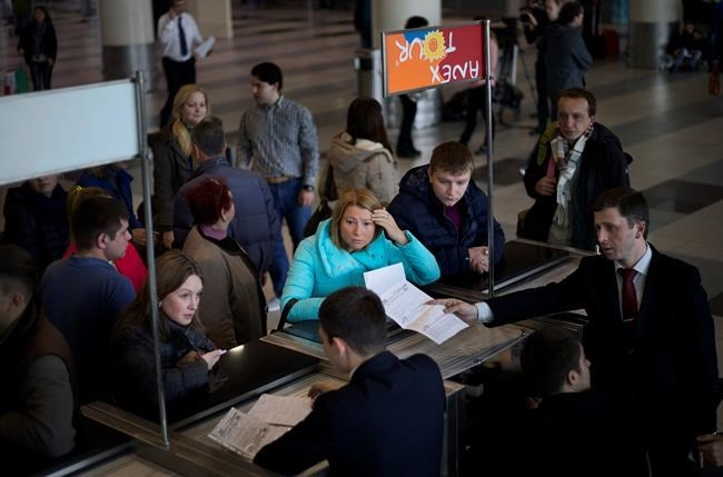 Travellers line up at a travel agency desk in Domodedovo airport in Moscow as their flight to Egypt is cancelled, on Saturday, Nov. 7, 2015. Russia has suspended all flights to Egypt until aviation security procedures improve, but some Russians apparently did not hear the news.