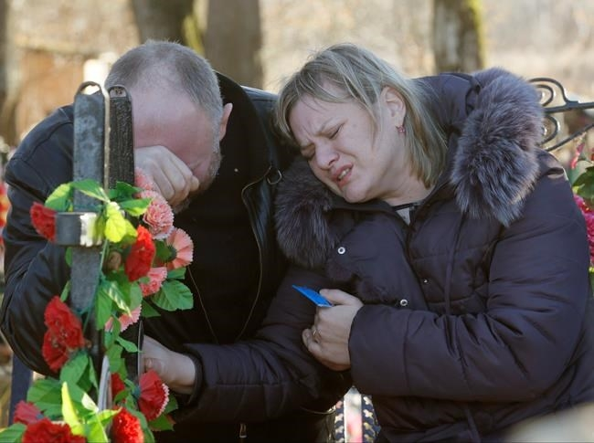 Nina Lushchenko's nephew Pavel and daughter Veronika react at her grave, after her funeral at a cemetery in the village of Sitnya, 80 km (about 50 miles) of Veliky Novgorod, Russia, Thursday, Nov. 5, 2015. The first victim of Saturday's plane crash in Egypt was laid to rest on Thursday following a funeral service in a medieval church in the north Russian city of Veliky Novgorod. Russia's Airbus 321-200 broke up over the Sinai Peninsula en route from the resort town of Sharm el-Sheikh to St. Petersburg, killing all 224 on board.