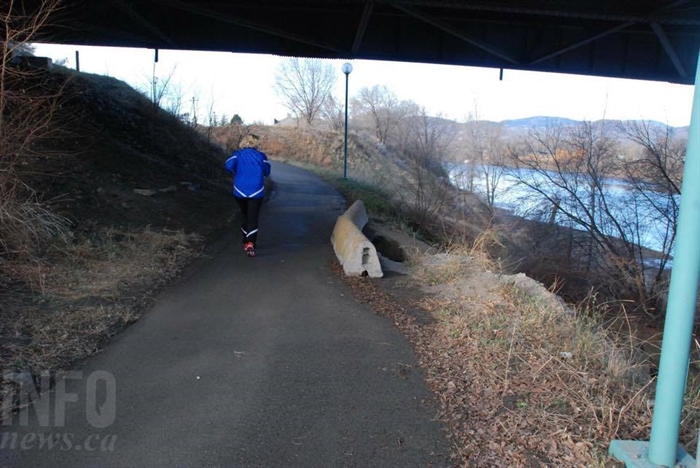 A jogger under the Yellowhead Bridge jogs past barricades blocking off the river banks erosion.