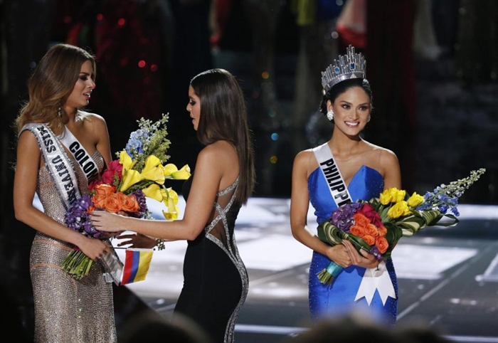 Former Miss Universe Paulina Vega, center, takes away the flowers and sash from Miss Colombia Ariadna Gutierrez, left, before giving it to Miss Philippines Pia Alonzo Wurtzbach, right, at the Miss Universe pageant Sunday, Dec. 20, 2015, in Las Vegas.