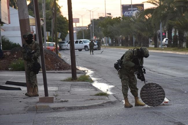 A Mexican navy marine inspects an open manhole after the recapture of Mexico's most wanted drug lord, Joaquin