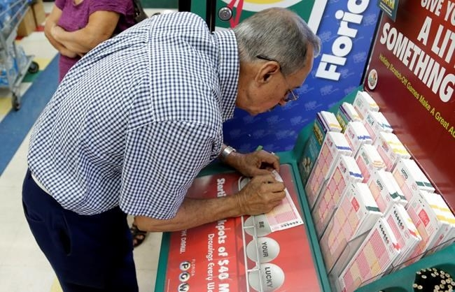 Julian Perez fills out a Powerball ticket, Saturday, Jan. 9, 2016, in Miami.