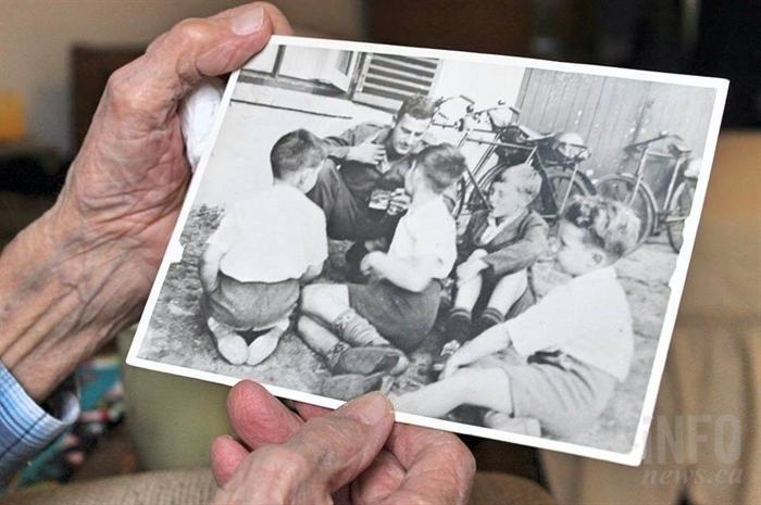 Ford holds his favourite picture from the war. It's from when he was visiting with some children outside a pub in England. The photo ended up in the Province newspaper and his mother cut it out to save for him.