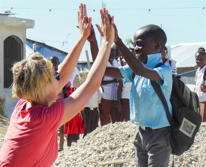 UBC Okanagan Human Kinetics student Paige Marzinzik high fives a young boy during her last visit to Haiti.