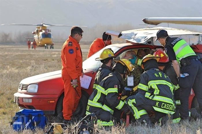A supervisor from RCAF's 442 Squadron watches on as local emergency crews work to help a Rocky Mountain Ranger with a fake neck injury. Crews pretended the car was the cockpit of an airplane involved in a airstrip collision.