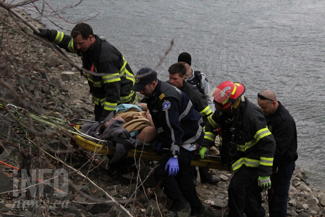 Members of Kamloops Fire Rescue, Kamloops RCMP and paramedics pull man up from river shore.