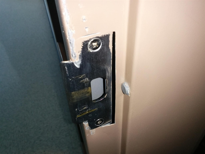The damaged metal plate and door frame.