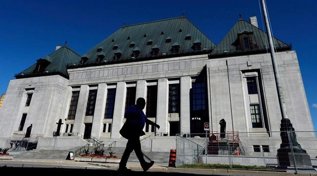 FILE PHOTO - A pedestrian walks past the Supreme Court of Canada in Ottawa on Thursday, July 23, 2015.