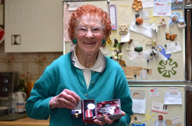 Helen Sidney holds just some of the awards she's received for community service over the years.