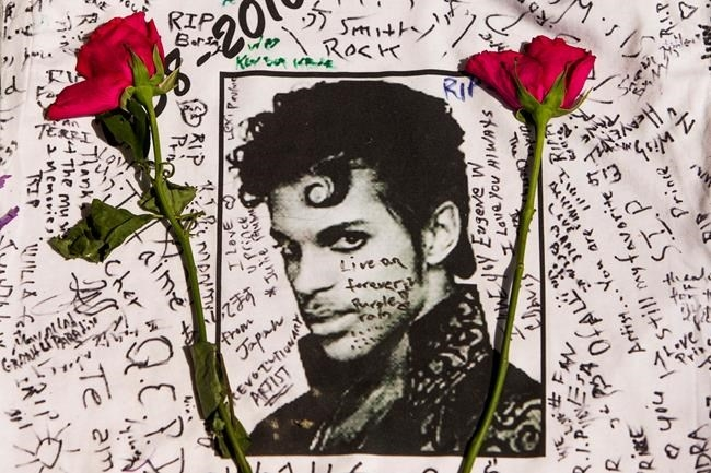 Flowers lay on a T-shirt signed by fans of singer Prince at a makeshift memorial place created outside Apollo Theater in New York, Friday, April 22, 2016. The pop star died Thursday at the age of 57.