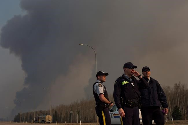 Police man a roadblock as smoke billows in the background near a wildfire in Fort McMurray, Alta., on Friday, May 6, 2016.
