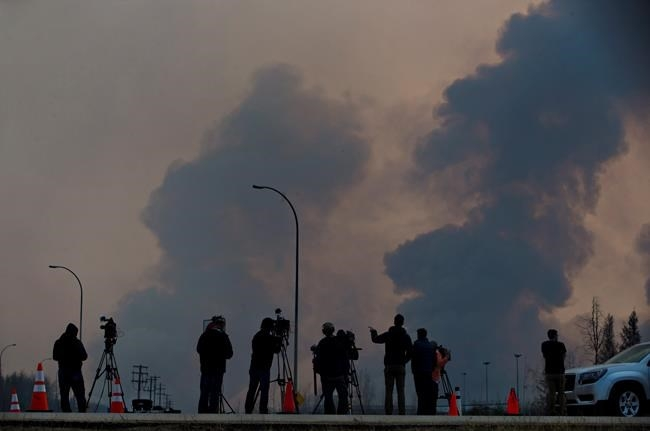 Media watch as smoke billows in the sky near a wildfire in Fort McMurray, Alta., on Friday, May 6, 2016.