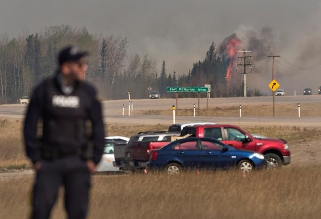 A police officer stands at a roadblock as a fire flares up near Fort McMurray, Alta., on Friday, May 6, 2016.