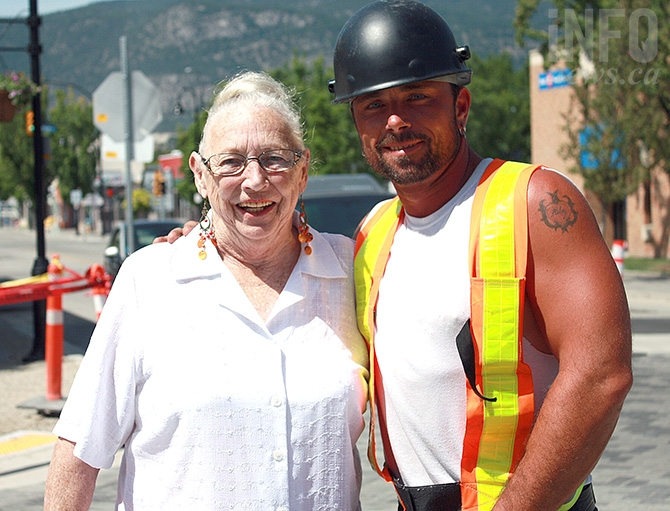 Penticton resident Lee Ballash gets a helping hand across the street while reconstruction efforts continue on Penticton's Main Street by Grizzly Excavating's Rob Kole.