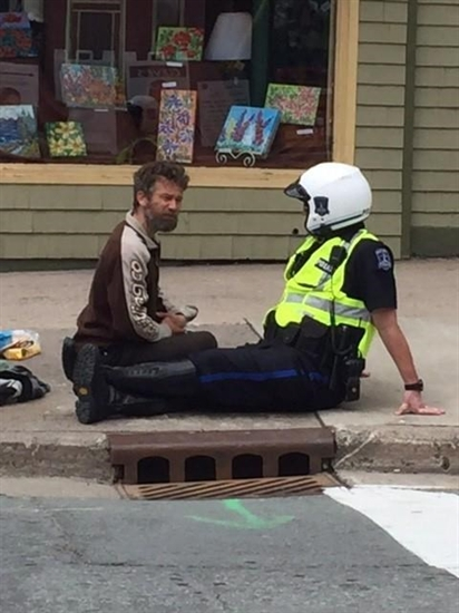 Community officer Const. Shawn Currie, right, sits down for a chat with a panhandler on the sidewalk in Halifax in this May 26, 2016, handout photo.