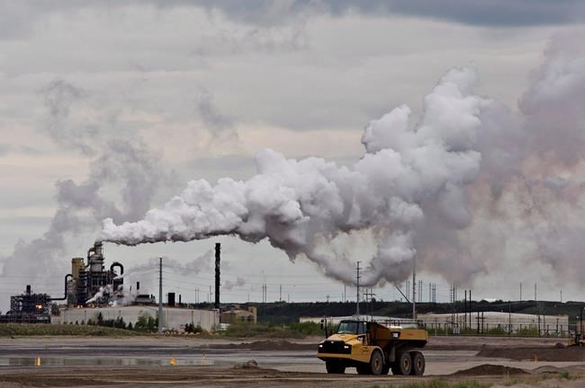 FILE PHOTO - A dump truck works near the Syncrude oil sands extraction facility near the city of Fort McMurray, Alta., on June 1, 2014.