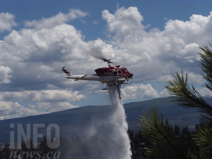 A helicopter drops a load of water on the wildfire burning on the hillside between Westside Road and Scott Crescent, Friday, June 17, 2016.