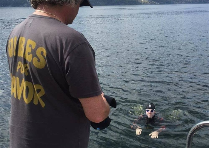 Adam Ellenstein, 39, is pictured during a break with one of his 20 support team members on his Okanagan Lake swim on Monday, July 25, 2016 in this Facebook photo.