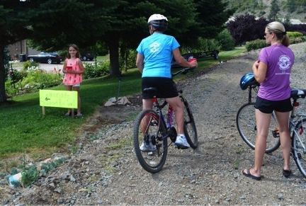 Taylor Denomme at Klub Kal offers lemonade to cyclists who are showing their support with rail trail t-shirts.