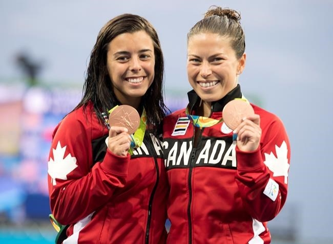 Canada's Meaghan Benfeito (left) and Roseline Filion celebrate on the podium after their bronze medal win in women's synchronized 10-meter platform diving at the 2016 Summer Olympics in Rio de Janeiro, Brazil, Tuesday, Aug. 9, 2016.
