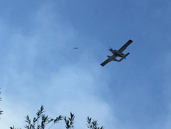 A bird dog circles overhead while the water bombers hit the fire.