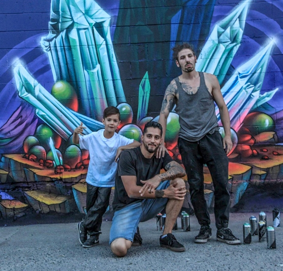 """Frisco"" Ugarte (centre), Karram Amro, along Frisco's son Tao, the organizers of the Fresh Coast Championship in front of the new mural on the wall of Hotel Zed that they also helped organize."