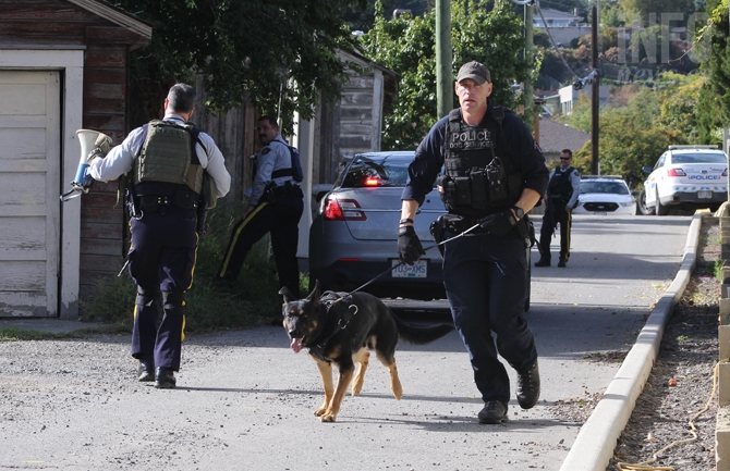 Kamloops RCMP officer and a police dog prepare to enter a house at 146 Columbia St., Monday, Sept. 26