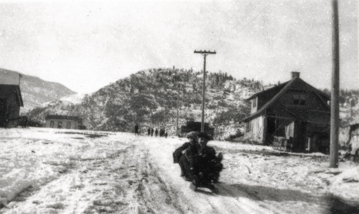 Children sledding down School Avenue in Oliver, including the B.C. Provincial Police Station (now the Oliver Museum) on the righthand side.