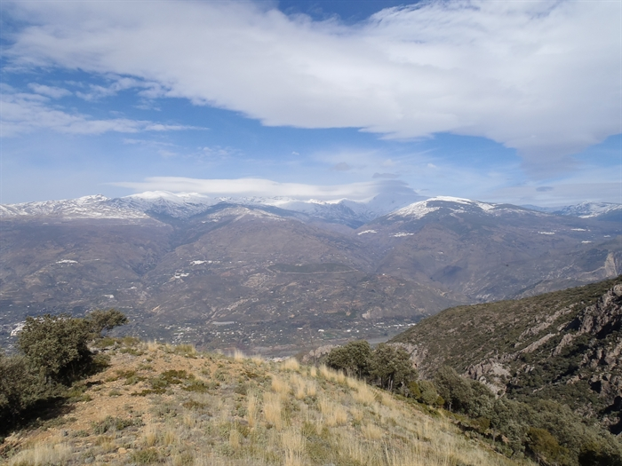 The white villages of Granada visible across the valley below the snow line.