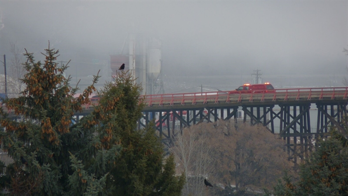 A Kamloops Fire Rescue truck is seen crossing the Red Bridge to reach the structure.