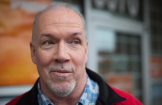 FILE PHOTO - British Columbia NDP Leader John Horgan speaks to a reporter after unveiling his election campaign bus in Burnaby, B.C., on Tuesday April 4, 2017.
