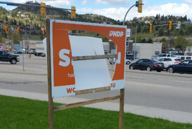 Both sides of a large campaign sign were cut by a vandal last week.