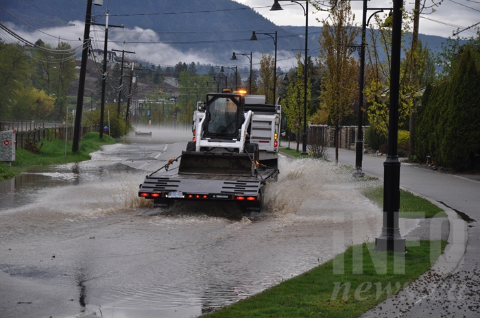 Work crews arrive to begin remediation work on Gellatly Road, covered by floodwaters.