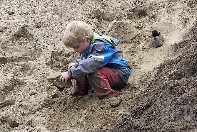 A Lake Country child empties sand from his shoes while his parents help shore up the banks of Duck Creek Thursday, May 11, 2017.