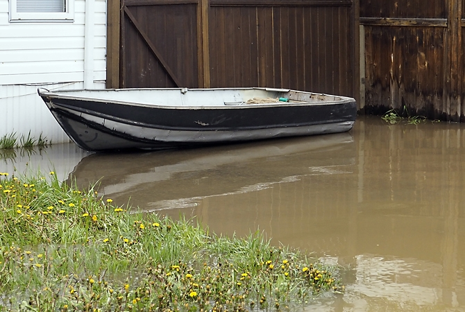 A boat floats in the front yard of a home under water on Commonwealth Road in Lake Country, Thursday, May 11, 2017.