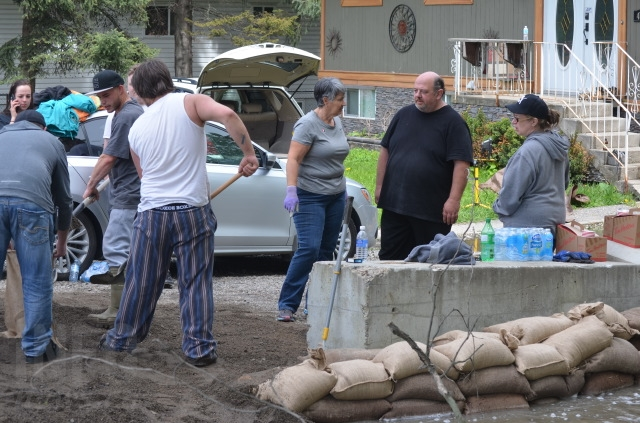 Members of the community chipped in to help Ted and Shannon Walker build sandbag dikes on their property along BX Creek in Vernon, Friday, May 12, 2017.