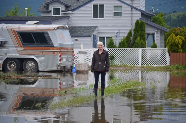 Solveig Anderson stands in water that has pooled around the Louis Estates neighbourhood on the Okanagan Indian Band reserve.