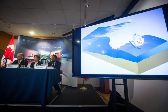 Animation of the capsizing of the whale-watching vessel Leviathan II off Vancouver Island in 2015 is played as Transportation Safety Board Manager of Marine Investigations Pierre Murray, from left to right, Chair Kathy Fox, and Investigator-in-Charge Clinton Rebeiro, watch during a news conference to release recommendations and findings of their investigation, in Vancouver, B.C., on Wednesday June 14, 2017.