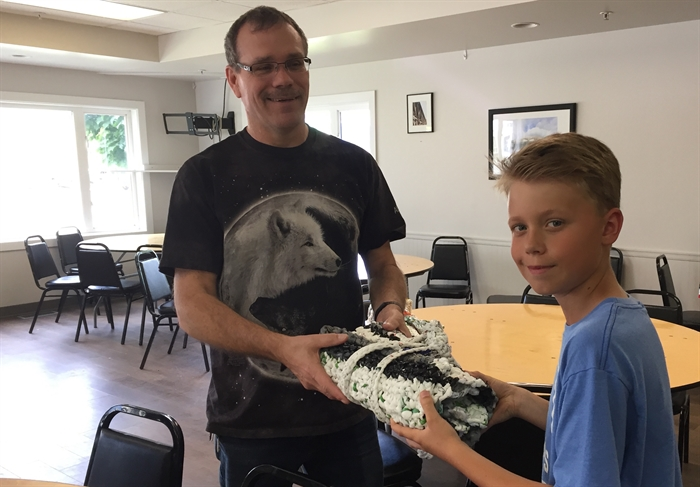 Froese's grandson Brody Passmore hands a completed mat to Regan, an outreach worker with New Life Community.