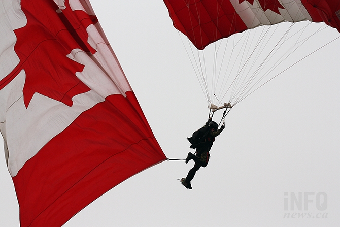 A Skyhawk parachutist trails a huge Canadian flag prior to landing in Okanagan Lake Park yesterday, Aug. 9, 2017.