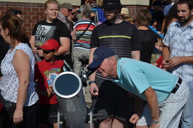 Blake Hanna takes an opportunity to view the eclipse through a telescope.