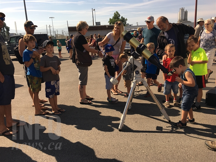 Children look through a telescope, provided by the Okanagan Centre of the Royal Astronomical Society of Canada, to view the solar eclipse in Kelowna, Monday, Aug. 21, 2017.