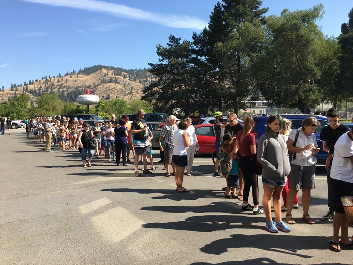 Hundreds of people line up at the Kelowna Curling Club to view the solar eclipse through a telescope provided by the Okanagan Centre of the Royal Astronomical Society of Canada, Monday, Aug. 21, 2017.
