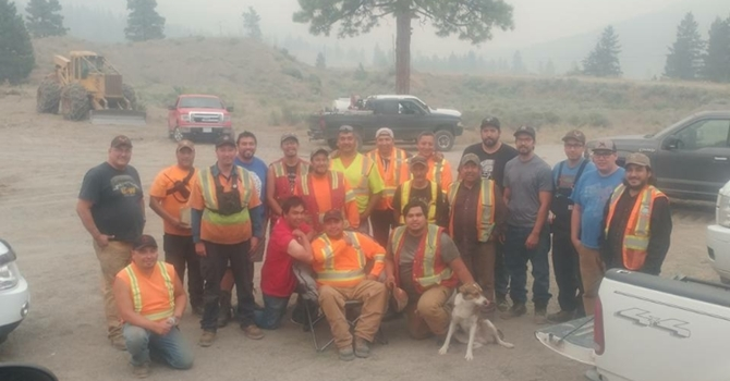 Brad Pierro (fifth in from right, wearing black shirt) and the twelve men who stayed to help fight the fire pose for a photo with some other men who came later to help keep things under control.