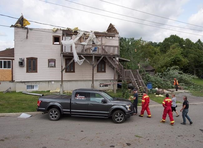 Residents survey the damage from a category one tornado, Wednesday, August 23, 2017 in Lachute, Que., northwest of Montreal.