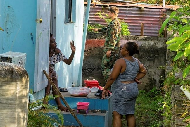 Two local women chat as a Dutch Marine helps out in preparation for the arrival Hurricane Maria, in Oranjestad, Statia, on the Leeward Islands, Monday, Sept. 18 2017. Maria has intensified into a Category 5 hurricane as its eye is approaching Dominica in the eastern Caribbean, the U.S. Hurricane Center said in a statement on Monday evening.
