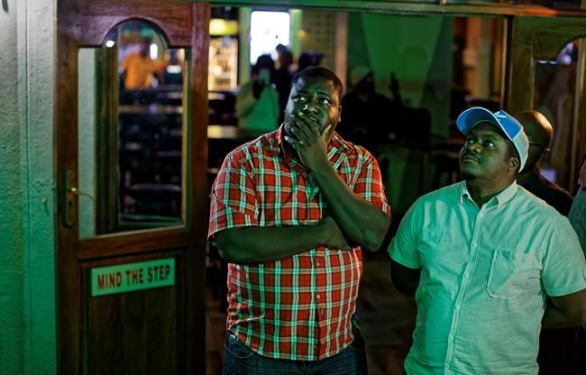 Disappointed Zimbabweans watch a televised address to the nation by President Robert Mugabe at a bar in downtown Harare, Zimbabwe Sunday, Nov. 19, 2017.